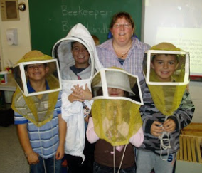children try on bee hats at a presentation